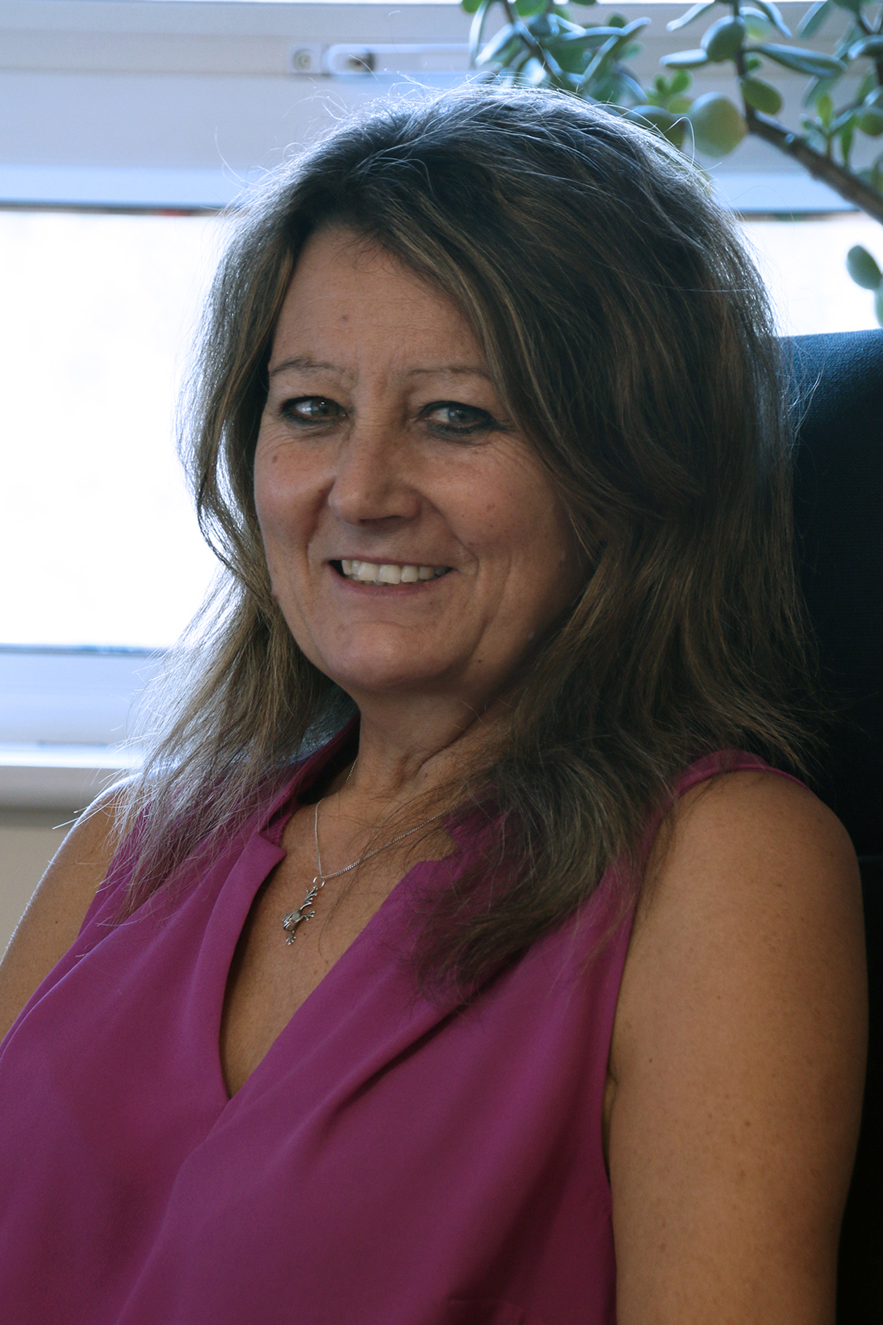 Lynda Moore sitting in office chair in front of a window, with a plant behind her. She wears a pink sleeveless shirt and is smiling