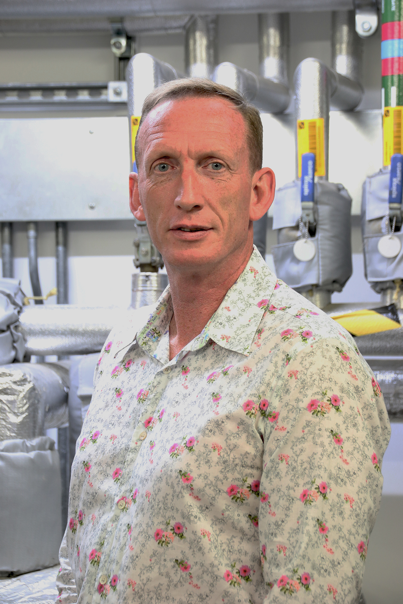 Dave Hamer wearing white shirt with small poppies, standing in effluent treatment plant at Pirbright, looking to camera