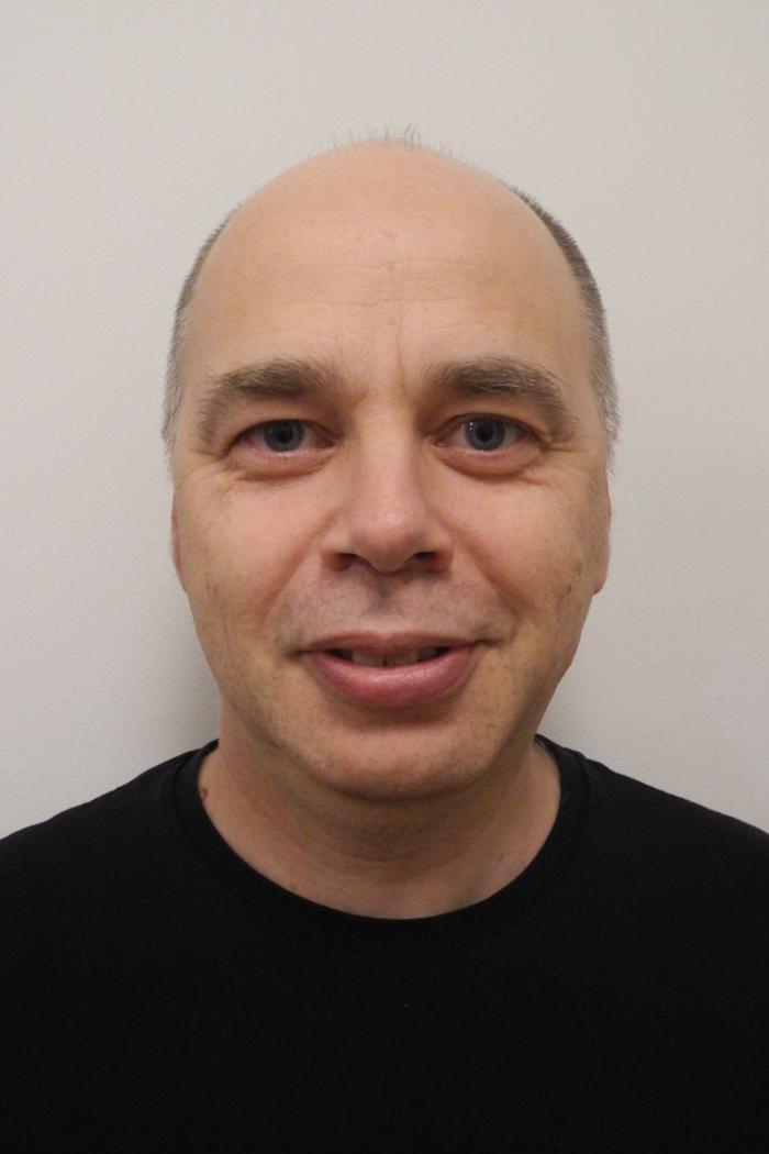 Dr Wilhelm Gerner, head and shoulders image, smiling and waering a black round neck t-shirt