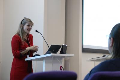 Lizzie Lockett in red top giving presentation at 2019 Culture of Care and 3Rs meeting