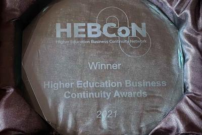 Round glass trophy in black satin presentation box, engraving on trophy reads: HEBCoN, Winner, Higher Education Business Continuity Network Awards, 2021