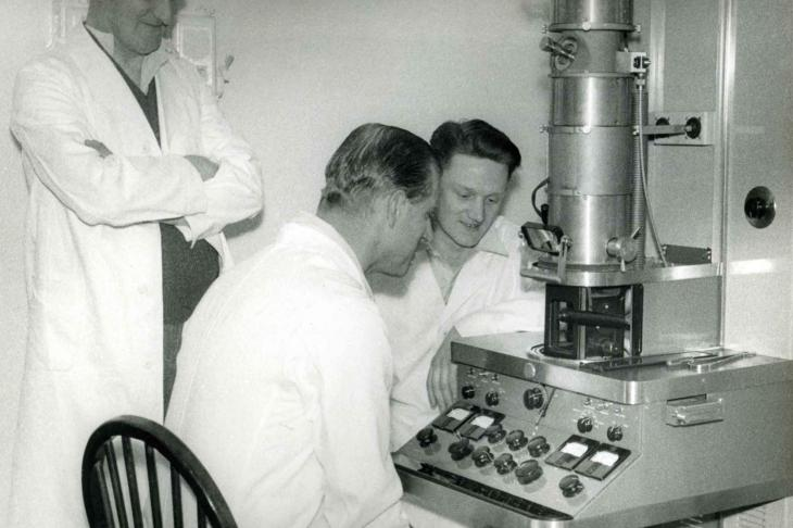 Prince Philip sits at early transmission electron microscope at Pirbright in 1956