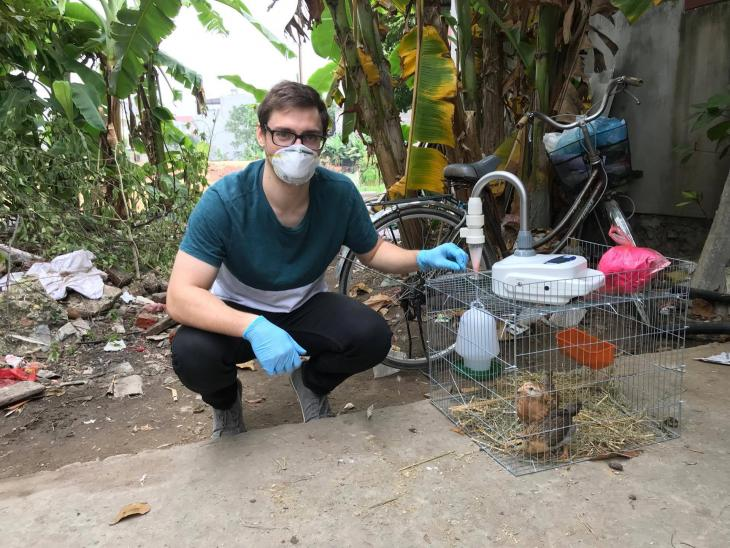 Joshua Sealy air sampling chickens for avian flu in Vietnam