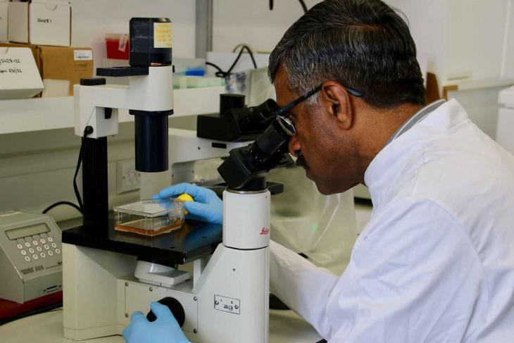 Professor Venu Nair looking down a microscope
